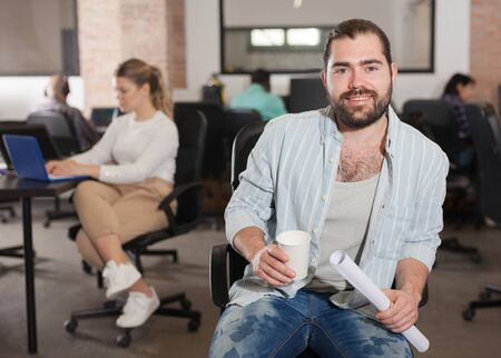 Portrait of smiling Latin hipster guy in coworking space with working colleagues behind