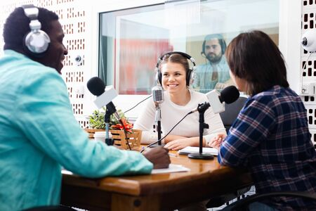 Multinational group of glad friendly smiling young adults emotionally discussing in radio studio