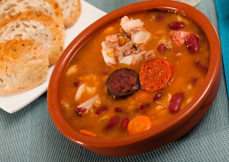 Traditional dish of Asturian cuisine - beans stewed with pork, blood sausage and chorizo (Fabada) served in clayware
