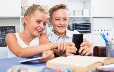 Girl is watching a video with a boy in his smartphone at home.