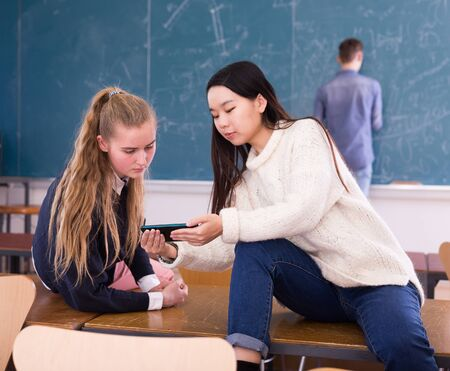 Portrait of happy student girls sitting with mobile phone on desk in schoolroom