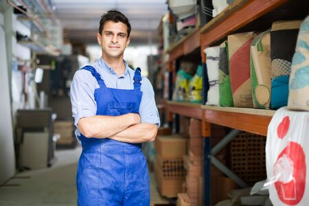 vendor in uniform on his workplace in building store.