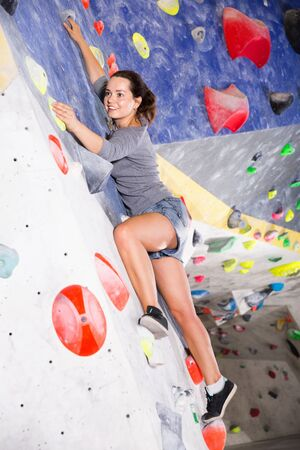 Glad cheerful smiling sporty woman training at bouldering gym without special climbing equipment