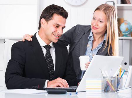 Businesswoman seducing male colleague while working on laptop in office