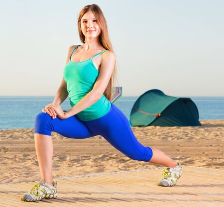 Smiling young glad pleasant beautiful woman in blue T-shirt is practicing stretching on the beach. 스톡 콘텐츠