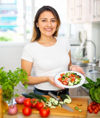 Portrait of smiling latino woman serving fresh healthy salad indoors in apartment