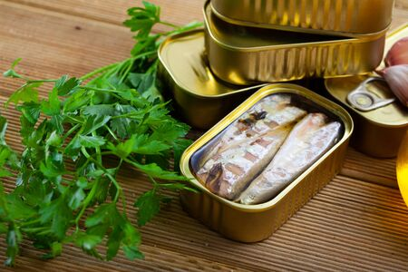 Preserved seafood, open can of tinned mackerel fish with condiments on wooden table