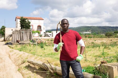 Confident african american male stands against the background of his farmhouse