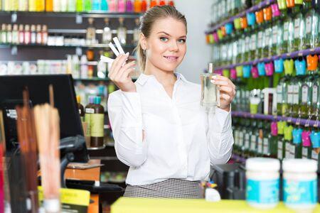 Smiling female seller showing perfume in cosmetic store Standard-Bild