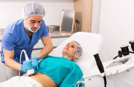 Young woman getting fat reductive skin lifting body treatment on modern equipment at cosmetology clinic Stockfoto