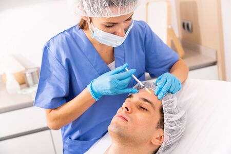 Young man patient of beautician receiving rejuvenating facial injections, concept of male aesthetic skin care
