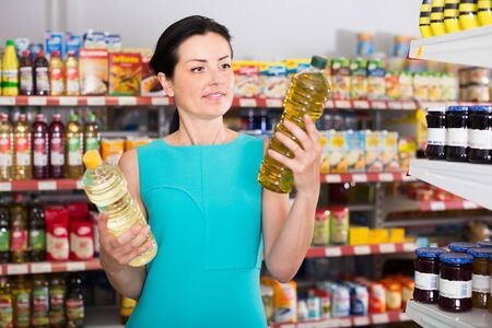 Nice female in the supermarket want to buying bottle of oil