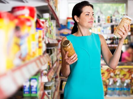 Adult woman readig label on glass jar of beans in the supermarket Stock Photo