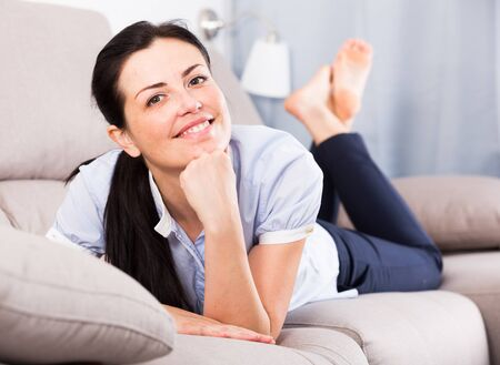 Smiling young female resting and dreaming on cozy sofa indoors