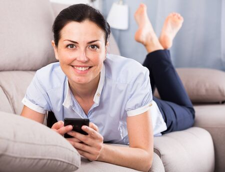 Young glad woman lying on cozy sofa with mobile phone at home