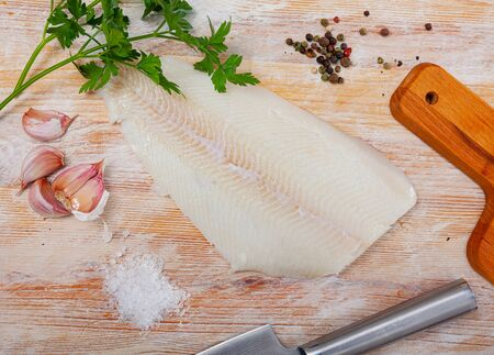 Image of fillet of raw halibut fish before cooking on wooden background with garlic