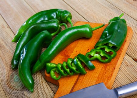 Fresh green bell peppers with chopped slices on wooden cutting board. Healthy vegetarian ingredient Imagens