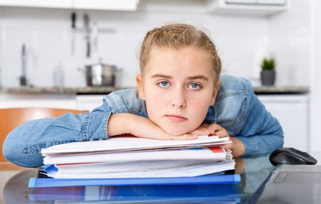 Tired teenage girl sitting at kitchen table among notebooks and schoolbooks