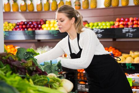 Young female grocery worker arranging fresh greens on store shelves