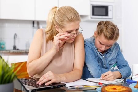 Positive mother helping her daughter with home task using laptop at kitchen table