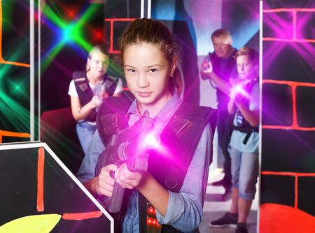 Excited girl aiming laser gun at other players during laser tag game in dark room