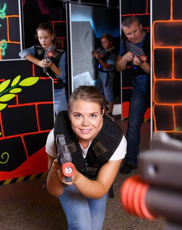 Excited young female aiming laser gun at other players during laser tag game indoors Stok Fotoğraf