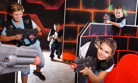 Group of happy kids and adults with laser guns playing on lasertag room
