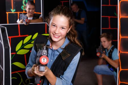 Glad girl aiming laser gun at other players during laser tag game in dark room