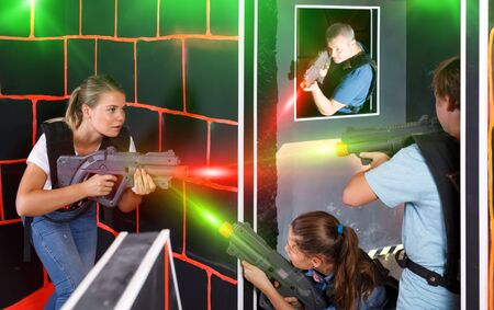 happy young parents and children with laser pistols playing laser tag in dark labyrinth