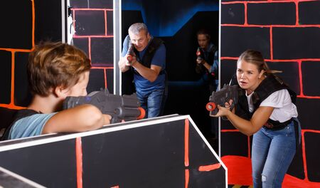 Modern parents and children with laser pistols playing laser tag in dark labyrinth