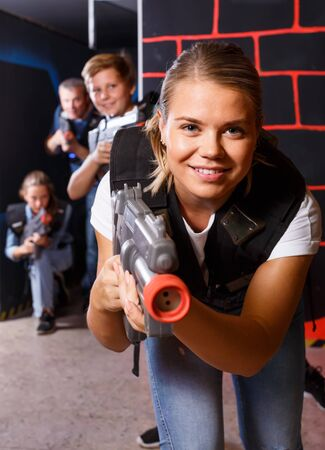 young girl with laser pistol playing laser tag with friends on dark labyrinth Stok Fotoğraf