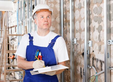 Focused construction diligent  friendly worker inspecting room and planning upcoming repairs