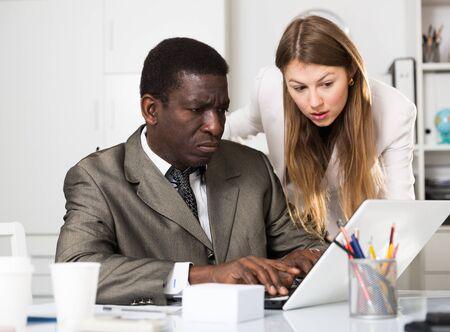 Young woman and man colleagues working at laptop and discussing in office Banque d'images