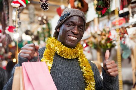Portrait of smiling African American man with shopping bags on festive fair before Christmas