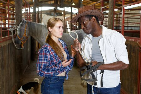 European girl and afro man who work at stable having emotional discussion