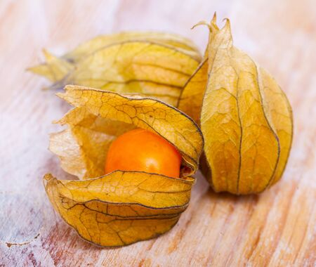 Whole orange berry fruits of cape gooseberries (physalis) on wooden table