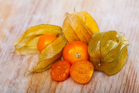Whole and cut in half orange berry fruits of cape gooseberries (physalis) on wooden table
