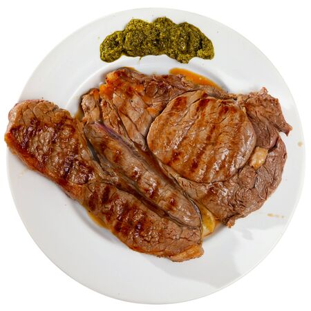 Delicious fried beef entrecote served with pesto sauce. Isolated over white background Stock Photo