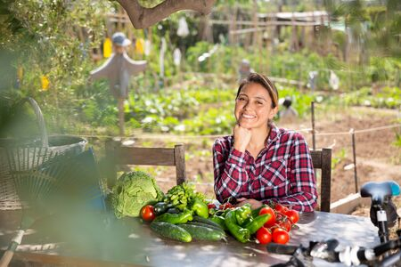 Young attractive Colombian woman sitting at table in homestead garden in sunny spring day, happy with harvest of vegetables