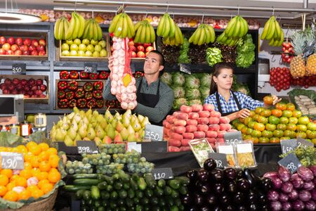 Male and female shop assistants laying out fruits and vegetables behind the counter on market