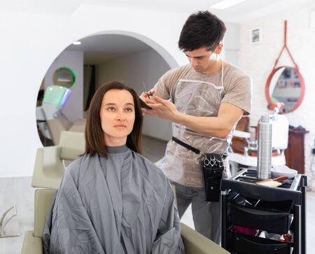 Young diligent positive cheerful smiling guy professional hairdresser cut woman's hair in hairdressing salon