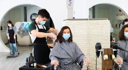 Young man professional hairdresser in mask cut female's hair in hairdressing salon