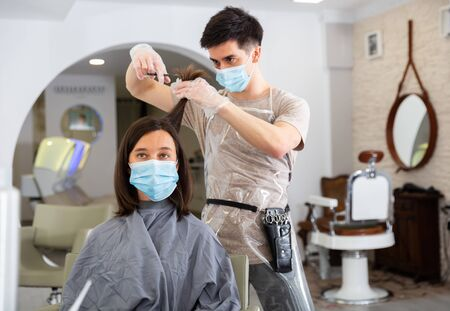 Young man stylist wearing face mask and gloves working in hairdressing salon doing haircut and hair styling for female client Stock Photo