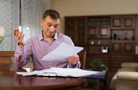 Emotional man calculating domestic budget and checking accountancy at home table Banque d'images