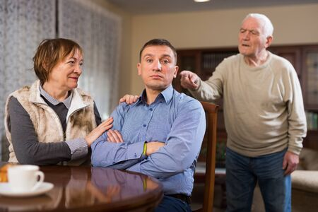 Senior man scolding his adult son in presence of mother in living room Stock fotó - 149359258