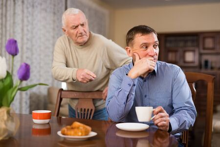 Frowning adult man listening to reprimanding from his aged father at home