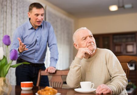 Offended elderly man sitting at table with disgruntled adult son standing behind and reprimanding him Stok Fotoğraf
