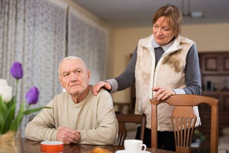Portrait of elderly wife and husband spending time together at home