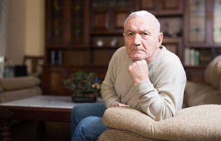 Portrait of senior man sitting on sofa at living room