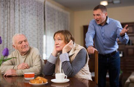 Adult annoyed man scolding his senior parents at home Stock fotó - 149359449